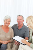Seniors with doctor at home — Stock Photo