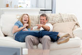 Lovers watching tv in the living room at home — Stockfoto