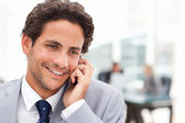 Charming businessman phoning in his office — Stock Photo