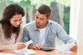 Giovane coppia calcolando le bollette domestiche — Foto Stock