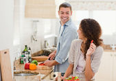 Beautiful woman looking at her husband who is cooking — Stock Photo