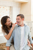 Lovers eating a strawberry in their kitchen — Stock Photo