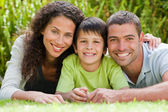 Little boy with his parents lying down in the garden — Stock Photo