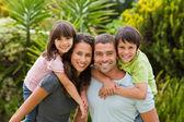 Moeder en vader geven kinderen een piggyback — Stockfoto