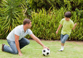 Son playing football with his father — Stock Photo