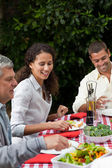 Happy family eating in the garden — Stock Photo
