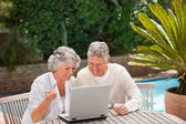 Retired couple buying something on internet — Stock Photo