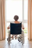 Mature woman in her wheelchair with her back to the camera — Stock Photo