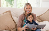 Mother looking at a book with her son — Stock Photo