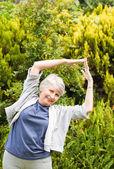 Reife Frau macht ihr erstreckt sich im Garten — Stockfoto