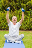Retired man doing his exercises in the garden — Stock Photo