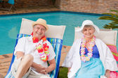 Senior couple lying down beside the swimming pool — Stock Photo