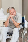 Smiling senior man in his wheelchair at home — Stock Photo