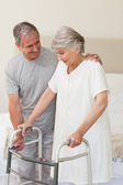 Man helping his wife to walk — Stock Photo