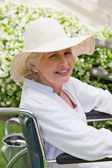Mature woman in her wheelchair in the garden — Stock Photo