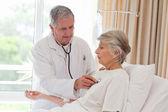 старший врач, принимая биение сердца своего пациента — Стоковое фото