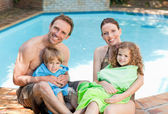 Portrait of a happy family beside the swimming pool — Stock Photo