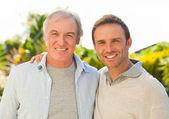 Ojca i syna, patrząc na kamery w ogrodzie — Zdjęcie stockowe
