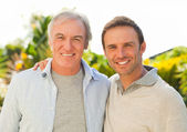 Vader en zoon kijken naar de camera in de tuin — Stockfoto