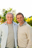Father and his son looking at the camera in the garden — Stock Photo