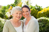 Mother with her daughter looking at the camera in the garden — Stockfoto