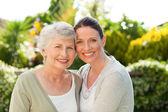 母亲与她的女儿看着花园里的相机 — 图库照片
