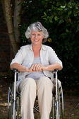 Smiling woman in her wheelchair — Stock Photo