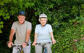 Senior couple mountain biking outside — Stock Photo