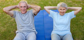 Retired couple doing their streches in the garden — Stock Photo