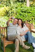 Lovers taking a photo of themselves in the garden — Stock Photo