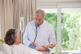 Senior doctor taking the blood pressure of his patient — Stock Photo