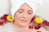 Relaxed woman taking a relaxing bath with a towel on her head — Stock Photo