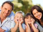 Familjen liggande i parken — Stockfoto