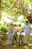 Casal com suas bicicletas na madeira — Fotografia Stock