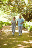 Couple running in the wood — Stock Photo
