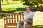 Elderly man sitting on a bench — Stock Photo