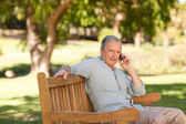 Retired man phoning in the park — Stock Photo
