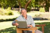 Retired man working on his laptop in the park — Stock Photo