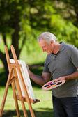 Senior man painting in the garden — Stock Photo