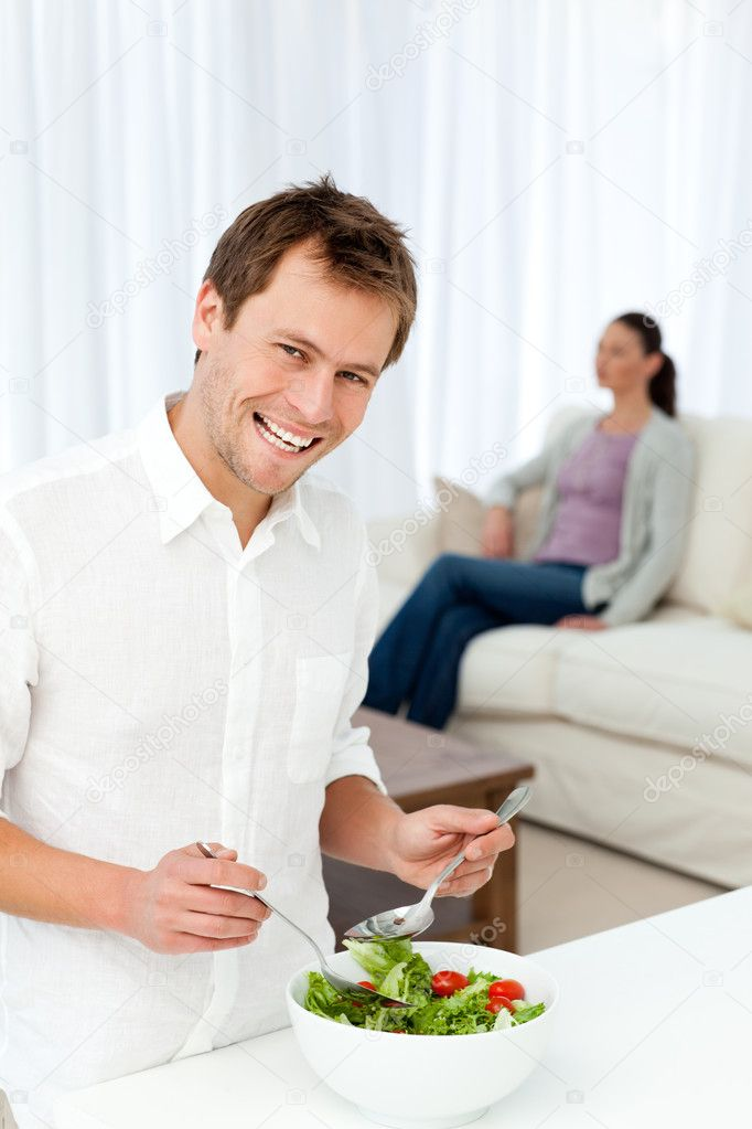 Happy man preparing lunch while his girlfriend relaxing on the sofa — Stock Photo #10840691