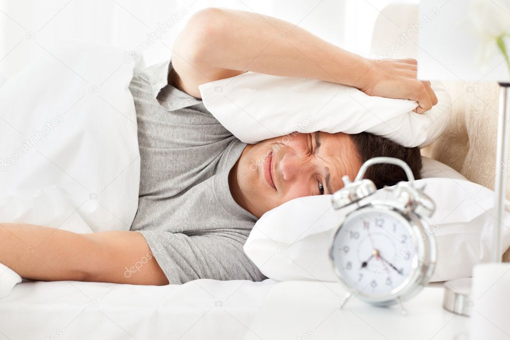 Stressed man looking at his alarm clock ringing while putting his head under the pillow — Stock Photo #10840863