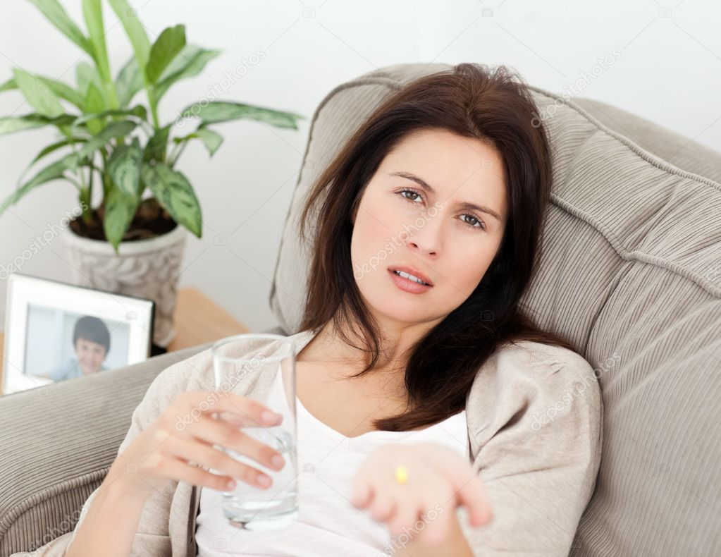 Tired woman taking her medicine lying on the sofa at home — Stock Photo #10840872