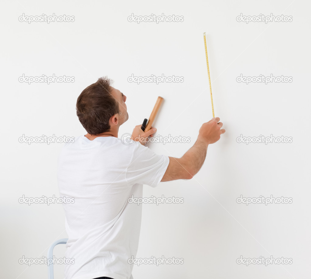 Handsome man looking at a wall with ruler and tools in his new room — Stock Photo #10840908