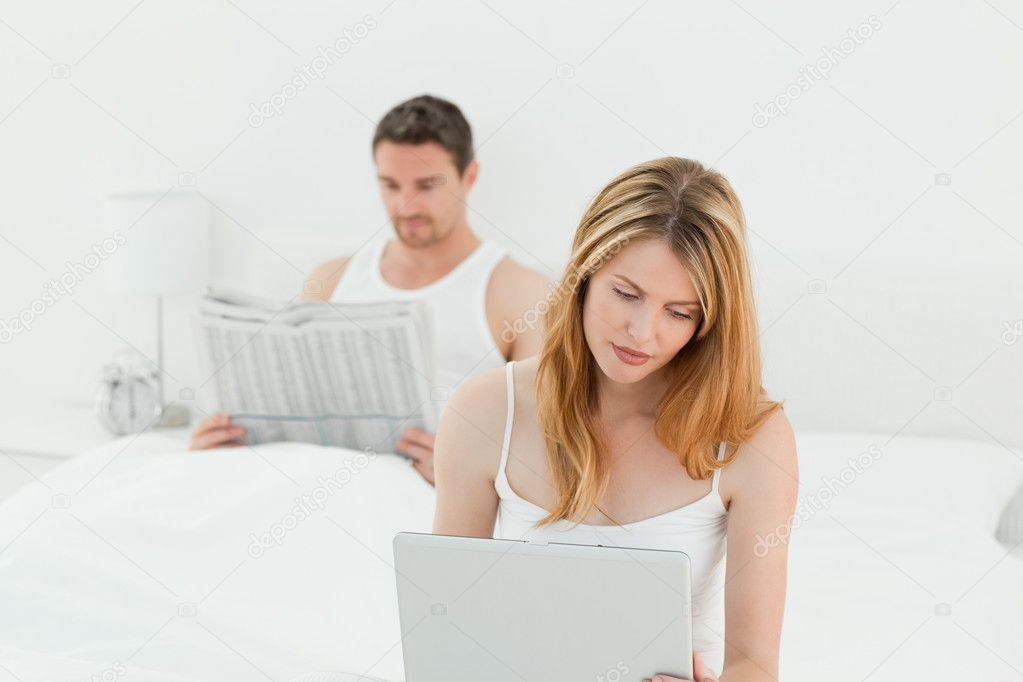Woman is on her laptop while her husband is reading newspaper in the bed — Stock Photo #10842179