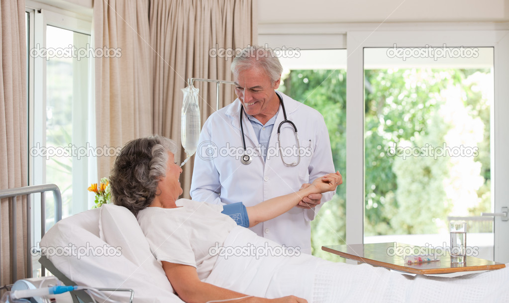 Senior doctor taking the blood pressure of his patient  Stock Photo #10848693