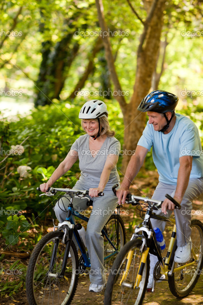 Elderly couple mountain biking outside — Stock Photo #10849792