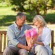 Mature man offering flowers to his wife — Stock Photo #10850032