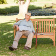 Senior man sleeping on the bench — Stockfoto