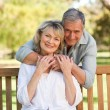 Stock Photo: Elderly mhugging his wife who is on bench