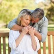Royalty-Free Stock Photo: Elderly man hugging his wife who is on the bench